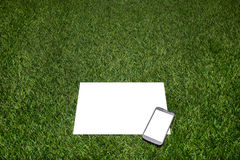 Mobile phone and sheet of paper lying on the grass Royalty Free Stock Photos