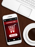 Mobile phone with shopping card page, mug of coffee and laptop Royalty Free Stock Photo