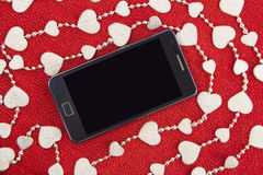 Mobile phone and the silver garland Royalty Free Stock Images
