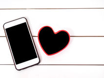 Mobile phone with small board heart Royalty Free Stock Images