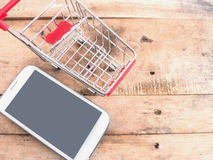 Mobile phone and small shopping cart Stock Photography