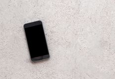 Mobile phone or smartphone with black screen on the cement floor royalty free stock photo