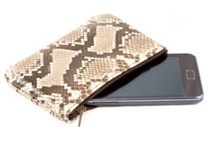 Mobile phone in the snake skin case Royalty Free Stock Images