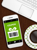Mobile phone with spring discount coupon, laptop and cup of coff Stock Images
