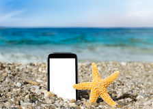 Mobile phone and starfish on the beach Royalty Free Stock Photography
