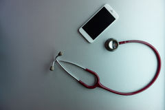 Mobile phone and stethoscope Stock Photos