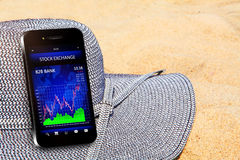 Mobile phone with stock chart on the beach Royalty Free Stock Photos