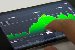 Mobile phone with stock chart. Hand touching stock chart on mobile phone Stock Image