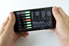Mobile phone with stock market. Man holding mobile phone with stock market screen Royalty Free Stock Photography