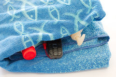 Mobile phone and sunblock in a beach towel Royalty Free Stock Photos