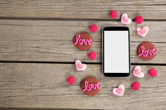 Mobile phone surrounded with cookies and confectionery. Displaying love message Stock Photos