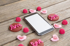 Mobile phone surrounded with cookies and confectionery. Displaying love message Stock Images