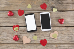 Mobile phone surrounded with heart shape decoration Stock Image
