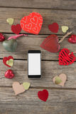 Mobile phone surrounded with heart shape decoration Royalty Free Stock Images