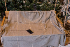 Mobile phone in a swing with a blanket in a snow-covered park Stock Photo