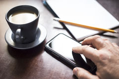 Mobile Phone on Table with Coffee on Side Royalty Free Stock Photography