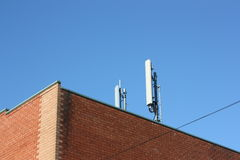 Mobile phone tower. Mobile cell phone tower on top of city building Stock Photography