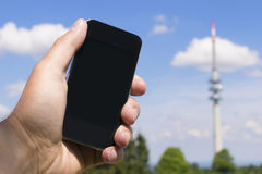 Mobile phone and transmission tower. Image of hand with mobile phone and broadcasting tower in the background royalty free stock photo