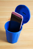 A mobile phone in a trash can. A pink mobile phone in a trash can royalty free stock photography