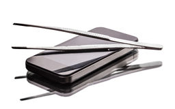 Mobile phone and tweezers. On a light background Stock Photos
