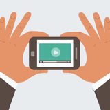 Mobile phone with video player. On the screen in the human hands Stock Images