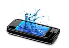 Mobile phone with water splashing out of the monit Stock Images