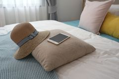 Mobile phone , weave hat and pale pink cushion on the blue bed s. Mobile phone , weave hat , pale pink cushion and blue fabric on the comfortable bed royalty free stock photos