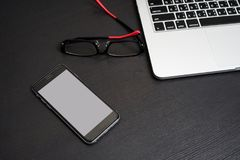 Mobile Phone white background with Laptop Keyboard and Eyeglasses Royalty Free Stock Image