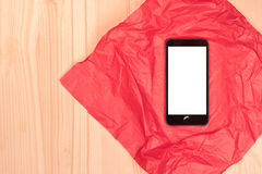 Mobile phone with white blank screen on red gift paper on wooden Royalty Free Stock Photo