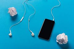 Mobile phone with white earphones on colour backgroungd. With rolled paper, top view royalty free stock images
