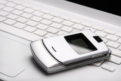 Mobile phone on a white laptop. Royalty Free Stock Photo