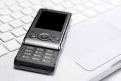 Mobile phone on white laptop keyboard. Modern mobile phone arranged with white laptop keyboard isolated on white background Stock Photos