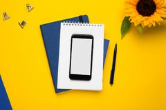 Mobile phone with white notepad , blue notebook and pen on yellow background royalty free stock image