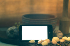 Mobile phone with white screen on table with spices Royalty Free Stock Photos