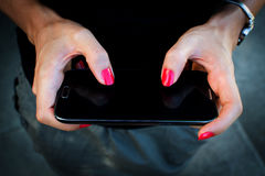 Mobile phone in woman hand Royalty Free Stock Photos
