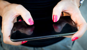 Mobile phone in woman hand Royalty Free Stock Photo