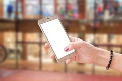 Mobile phone in woman hand with isolated screen for mockup. Business center in background royalty free stock photo