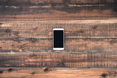 Mobile phone on the wood desk.  Stock Photo