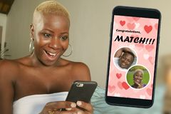Mobile phone and young beautiful and happy black afro American woman using online dating app excited in match with a handsome guy royalty free stock photography