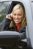 Mobile Phonecall. A beautiful young woman sitting in her expensive black 4 x 4 vehicle and talking on her mobile phone Stock Images