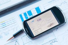 Mobile phones and charts of financial growth on the desktop. Business concept royalty free stock image