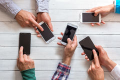 Mobile phones in friends hand. Closeup. Network addicted concept Royalty Free Stock Images