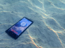 Mobile phones on the sand under the sea water. Mobile phones on the sand with light reflected under the sea water Royalty Free Stock Images