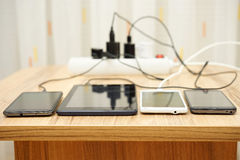 Mobile phones and tablet  charging on desk.  Royalty Free Stock Images