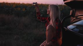Mobile photography, sexy woman take a photo of sunflower field. At sunset sitting on a car stock video