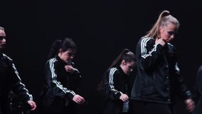 Mobile pretty girls in black sportive black clothes dance on stage at festival. Band of energetic pretty young women wearing black sport clothes synchronically stock video footage