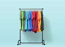 Mobile rack with color clothes on light blue background. File contains a path to isolation. Royalty Free Stock Photo