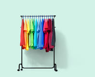 Mobile rack with color clothes on light green background. File contains a path to isolation. Stock Image