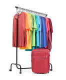 Mobile rack with colorful clothes and a suitcase on white background. File contains a path to isolation Stock Image