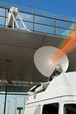 Mobile satellite dish and beam. Mobile satellite dish on a van or car in an urban environment in front of modern architecture, used by the news media to cover Royalty Free Stock Images